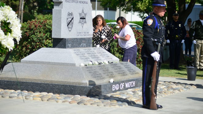 Family of fallen officers placed flowers at the Peace Officers Memorial during an event to honor the fallen Wednesday in Visalia.