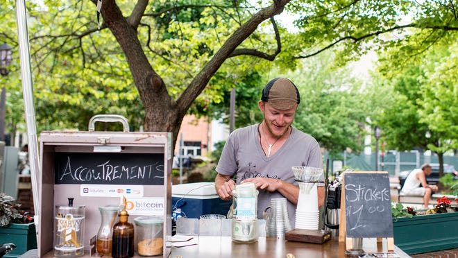 Ryan Prentiss, owner and founder of The Coffee Pedlar, makes an iced pour over coffee at his stand at Pritchard Park in downtown Asheville earlier this month. His is one of few businesses in town accepting payment in the form of Bitcoin.