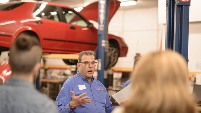 Jerry Elman,, center, owner of Schoen Place Auto, hosts the monthly members' networking event at his shop in Pittsford on May 12.