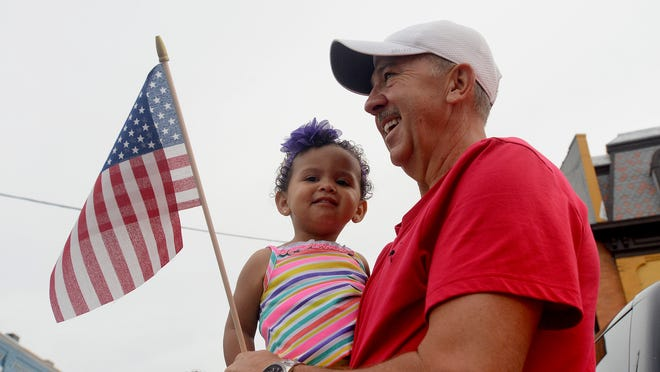 Tim Alverson, 56, of Williamston, holds his granddaughter, Harlow Alverson, 2, on Monday as they watch the Williamston Memorial Day parade go by. Tim's father, Percy Alverson, served in World War II, was at Normandy on the second day of the invasion, received a Purple Heart, and marched in the Williamston Memorial Day parade every year until he passed in 2011.