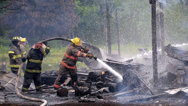 Crews work to knock out hot spots Wednesday at the remnants of a barn along M-99 in Eaton Rapids Township.