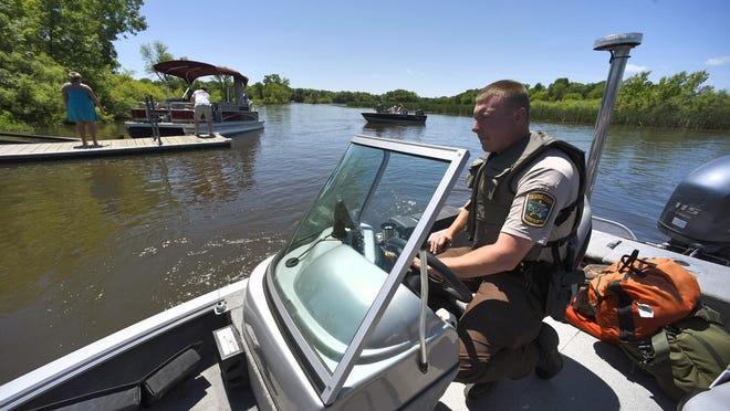 Stearns County Sheriff's Deputy Aaron Wells cruises Sunday past the public access on Horseshoe Lake near Richmond. The water patrol has four boats regularly on patrol around the county lakes.