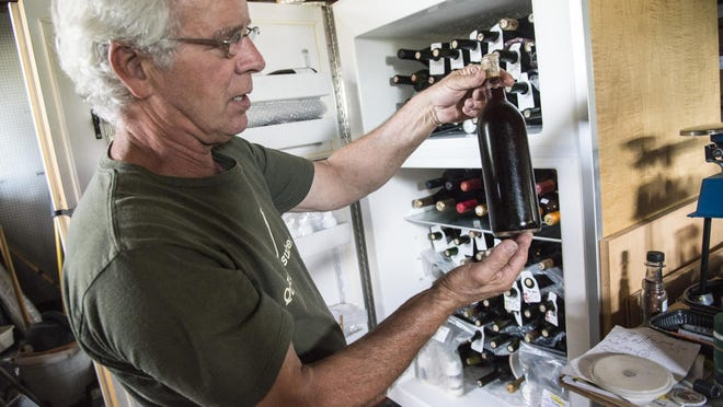 Tom Mincarelli ages his wine, including this bottle of Merlot bottled in 2010, carefully in a cooled space in his workshop.
