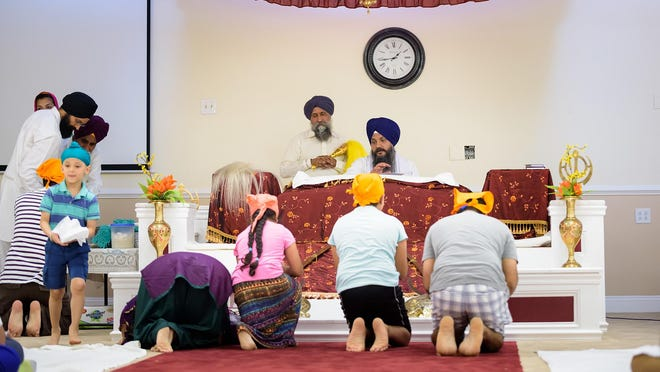 Sunday's gathering at the Gurdwara of Delaware included religious readings as worshipers paid respect and a special bread was prepared as a religious offering. Here, Lakhvinder Singh Khalsa (left) stands behind Gurbinder Singh Virdi, who is reading.