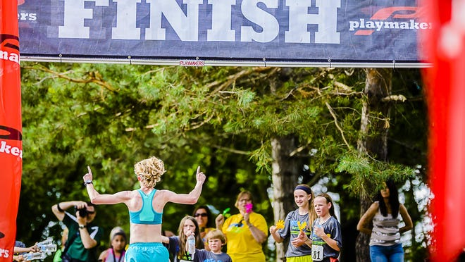 A runner celebrates as she crosses the finish during the 2015 Capitol 5K in Lansing.