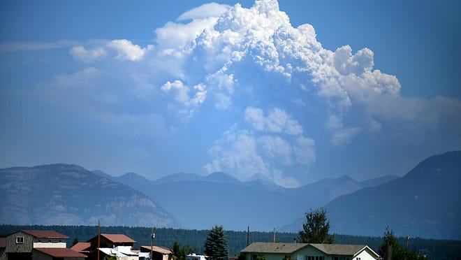 Plumes of smoke from the Thompson fire in Glacier National Park rise into the sky, seen from Lost Creek Road and Farm-to-Market Road west of Kalispell on Tuesday.