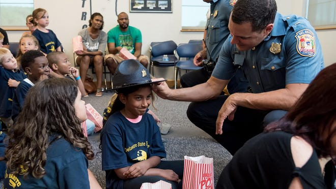"Lt. Jeffrey Whitmarsh shares his trooper hat with Hareesha Baranidharan, 8, of Hockessin, before they watch ""Penguins of Madagascar"" at the debut Community Movie Nights event hosted by Delaware State Police and the Delaware State Troopers Association at Troop 2 in Glasgow."