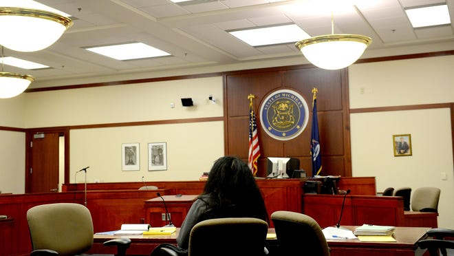 A defendant sits alone during a break as the judge and attorneys conference in the judge's quarters during a child protection hearing in Judge George Economy's Ingham County courtroom last month. Economy listened to testimony in cases dealing with whether parents should have their parental rights taken away.
