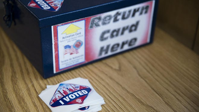 """After casting their ballots, voters in Clark County deposit the cards they use to vote in this box and receive an """"I voted"""" sticker that resembles the Las Vegas welcome sign."""