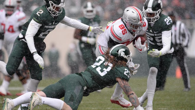 Junior linebacker Chris Frey (23) tackles Ohio State tight end Marcus Baugh with help from freshman Donnie Corley (29) during the Spartans' 17-16 loss to the Buckeyes.