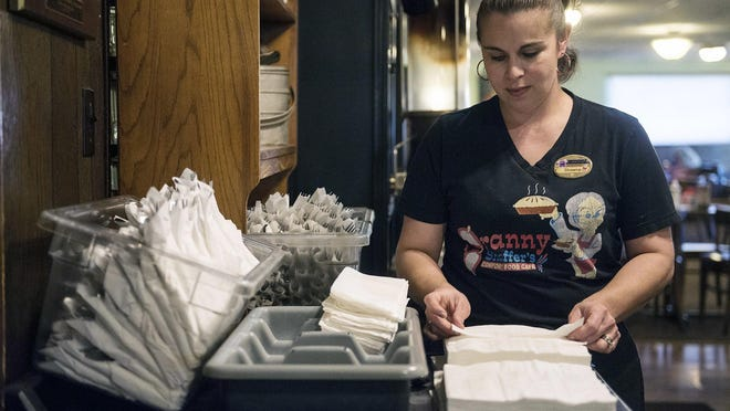 In this Tuesday, Dec. 18, 2018 photo, Shawna Green, waitress at Granny Shaffer's, prepares utensils for customers at the restaurant in Joplin, Mo. Wages will be increasing for millions of low-income workers across the U.S. as the new year ushers in new laws in numerous states. In Missouri and Arkansas, minimum wages are rising as a result of voter-approved ballot initiatives.