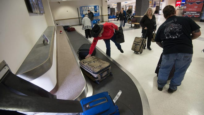 Travelers pick up their bags at the baggage carousel at the Coastal Carolina Regional Airport in this file photo.