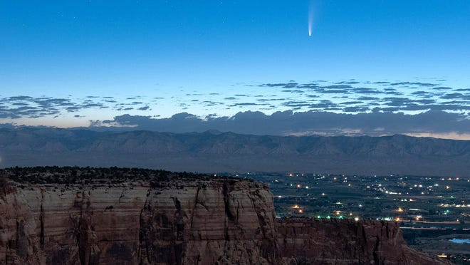 Comet Neowise soars in the horizon of the early morning sky in this view from the near the grand view lookout at the Colorado National Monument west of Grand Junction, Colo., Thursday, July 9, 2020. The newly discovered comet is streaking past Earth, providing a celestial nighttime show after buzzing the sun and expanding its tail.