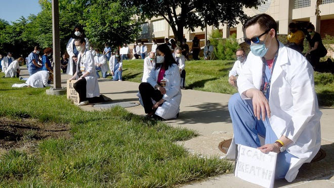 "Jin Cai, a physician at University Hospital, kneels with a sign that says ""I can't breathe"" at the White Coats 4 Black Lives demonstration Thursday next to Stankowski Field."