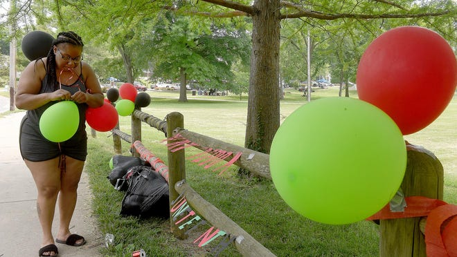 Janay Bennett decorates a fence in Douglass Park last year to celebrate Juneteenth.