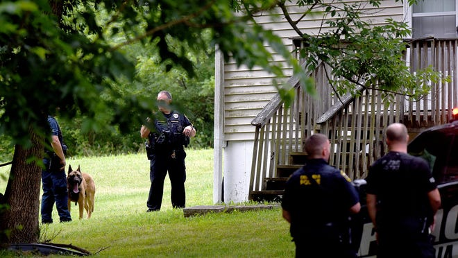 Columbia police officers surround a house at 1128 Westwinds Drive after they used a dog to track a man there and found him unconscious. He earlier had led police on a high-speed chase, which was terminated before he crashed the car he was driving at Stadium Boulevard and West Boulevard about 11:10 a.m. He allegedly tried to enter a car stopped at the intersection but was unsuccessful, police said.