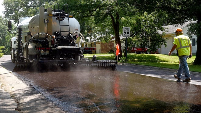 Columbia street department workers spread oil Wednesday before laying three-quarter-inch Mountain Trap rock on Concordia Drive. For a full list of streets scheduled to be chip sealed go to bit.ly/como-chip-seal.