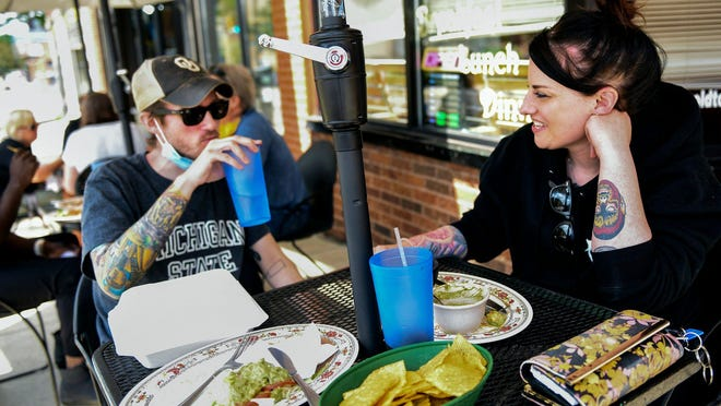 Amy Michael, right, and her friend Josh Burbank enjoy lunch outside at Pablos's Old Town Mexican Restaurant on Tuesday, June 16, 2020, in Lansing.