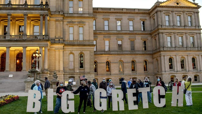 """A group stands behind a large sign reading """"Big Gretch"""" during a rally in support of Gov. Whitmer on Thursday, Oct. 8, 2020, at the Capitol in Lansing."""