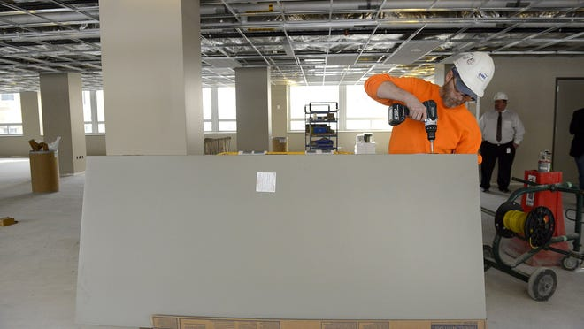 Rich Elmer of HBC Contracting gets doors ready to be hung in the renovated Mason Building in Lansing earlier this month.