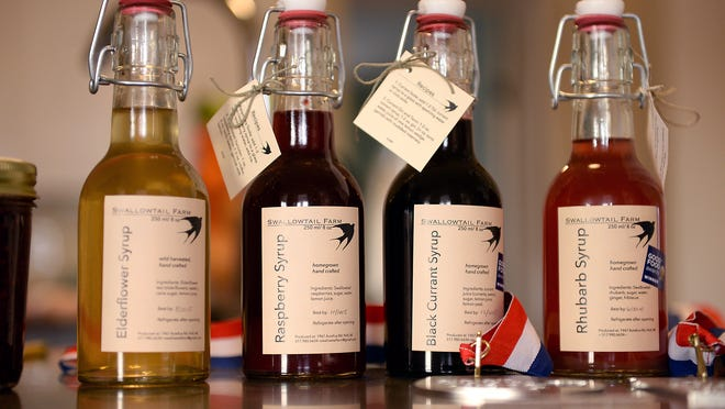 Four of the Swallowtail Farm syrups sit on the counter of Anne Rauscher's 1860s farmhouse in Mason. The syrups are next to two awards Swallowtail Farm have received for the syrups, most recently for the Black Currant syrup.
