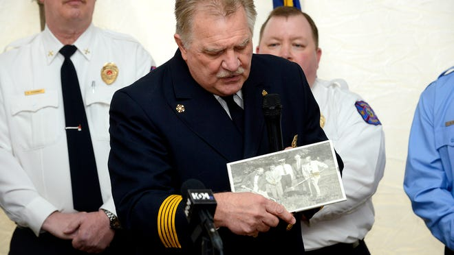 Meridian Township Fire Chief Frederick Cowper holds a photograph of the groundbreaking of the original central fire station while speaking Tuesday at the groundbreaking for the new central fire station at Okemos Road and Central Park Drive. Cowper said the photo will hang in the new fire station.
