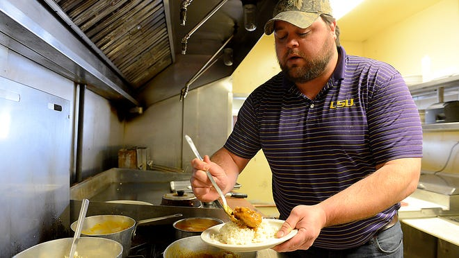 Brandon Whitt, Jumbeaux's head chef who moved to Michigan from Louisiana, plates up a smothered chicken dish. The dish is one of many southern and Cajun foods offered at the restaurant.