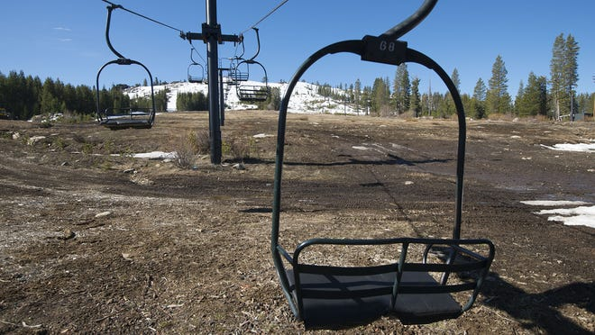 Ski lift chairs sit idle at shuttered Soda Springs on March 18 in Soda Springs, Calif. Warm winter weather has sped up the closure of several Tahoe area ski resorts.