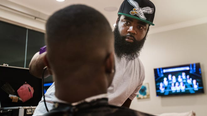 Rochester checks his line as he cuts Eagles wide receiver and kick returner Josh Huff's hair in Huff's Philadelphia apartment, earlier this month.