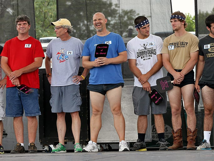 Some of the contestants for the Mr. Legs contest lined up on the Bud Light stage at the Iowa State Fair in Des Moines on Saturday August 9, 2014.