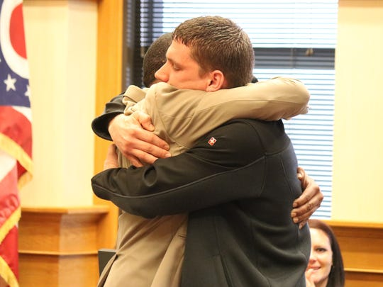 Kenn Bower, right, executive director of Light House Sober Living, hugs recent Drug Court graduate Damion Tall.