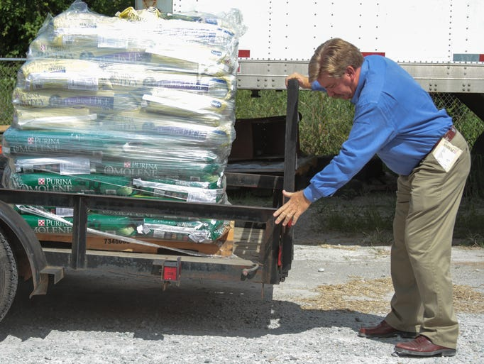 Purina Sales Specialist Rusty Bane closes the tailgate on a trailer loaded with feed for Redemption Road Rescue which was donated by Jim Mills.