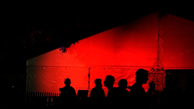 People walk past the VIP tent which is glowing with red lights at night Bonnaroo Music and Arts Festival on Thursday  June 11, 2015.