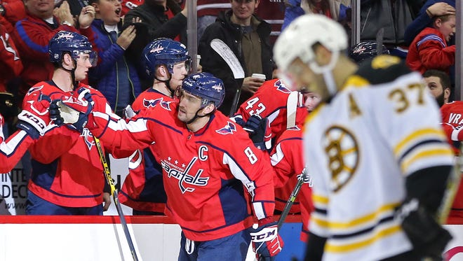 Washington Capitals forward Alex Ovechkin (8) celebrates with teammates after scoring a goal against the Boston Bruins in the second period at Capital One Arena.