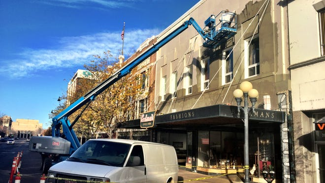 Crews with Montana Flex-Teriors restory stucco on outside of downtown Beckman building for Feather Your Nest shop owners Kandy and Lewis Zanto.