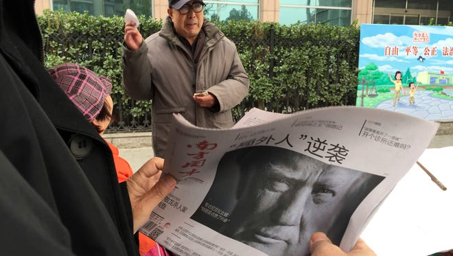 """A man holds up a Chinese newspaper with the front page photo of U.S. President-elect Donald Trump and the headline """"Outsider counter attack"""" at a newsstand in Beijing on Nov. 10, 2016."""