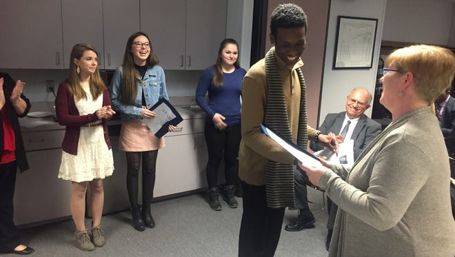 Canton High School senior Terrill Malone accepts a handshake from Plymouth-Canton school board Vice President Kate Borninski, while the other STARS winners -- senior Kendall Milo, junior McKenna Pierce and senior Sydney Good -- look on.