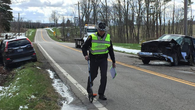 A state trooper investigates a head-on crash that left two people injured on Ohio 546 near Kings Corners Road on Friday afternoon.