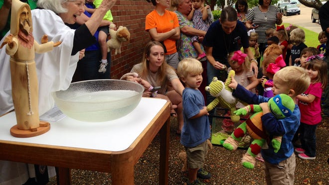 The Rev. Elizabeth Ratcliff blesses a stuffed frog and Teenage Mutant Ninja Turtle for Henderson Fowlkes, 2, in honor of the feast day of St. Francis of Assisi at St. James Episcopal Day School on Friday. Henderson is the son of Nick and Stevie Fowlkes.