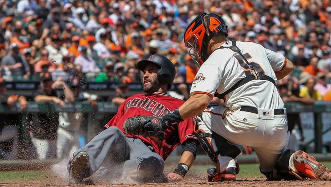 Arizona Diamondbacks right fielder J.D. Martinez (28) gets tagged out at home plate by San Francisco Giants catcher Nick Hundley (5) during the fourth inning at AT&T Park.