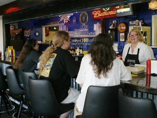 Chantal Saunders laughs with customers from behind