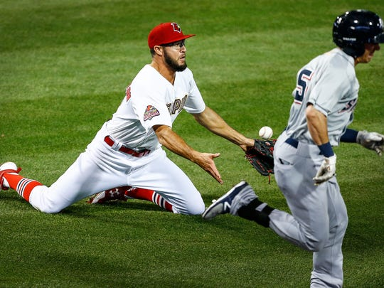 Memphis Redbirds pitcher Daniel Poncedeleon (left) makes a sliding throw for an out during action of the team's home opener against Colorado Springs at AutoZone Park, Tuesday night.