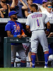 New York Mets' Jose Reyes, left, congratulates Amed Rosario, who had a hit in his debut in the majors, off Colorado Rockies reliever Scott Oberg duirng the eighth inning of the baseball game Tuesday, Aug. 1, 2017, Denver. The Rockies won 5-4. (AP Photo/David Zalubowski)