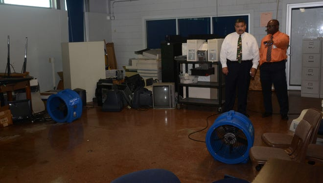 Roy Rachal (left), over risk management for the Rapides Parish School District, and Clyde Washington, deputy assistant superintendent, look over one of the classrooms at Arthur F. Middle Magnet School, which experienced flooding during Thursday's storm.