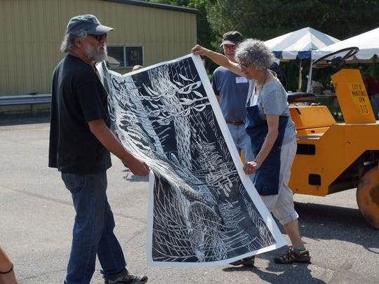 Art Professor Berel Lutsky (left) from UW-Manitowoc and Art Professor Emeritus Stephanie Copoulos-Selle from UW-Waukesha with one of the Really Big Prints created with the help of a steamroller at the printmaking event in 2014.