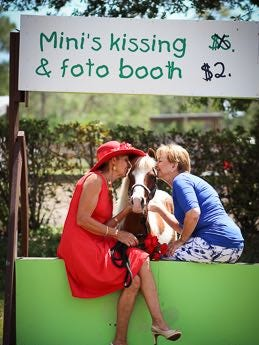 Dolores Kennedy, left, and Beverly Bevis Jones give Caesar, a painted mini-horse, a kiss in the kissing booth. The kissing booth will be open for the Kentucky Derby Day party May 5.