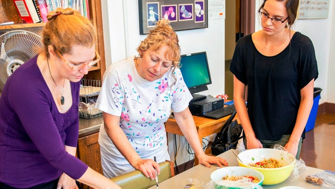 Registered dietitian Christine Evans (left) and Lisa Stark, associate professor of dietetics, work with Vanessa Lawrence, a dietetics graduate student at Mount Mary University, to develop healthy recipes that use items common in food pantries.
