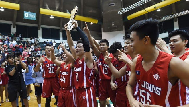 The St. John's School Knights celebrate their Independent Interscholastic Athletic Association of Guam Boys' Basketball Championship game victory over the St. Paul Warriors at the University of Guam Calvo Field House on March 9, 2018.