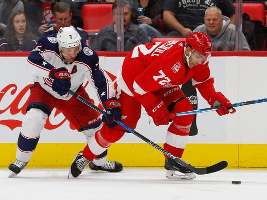 Columbus Blue Jackets defenseman Jack Johnson (7) and Detroit Red Wings left wing Andreas Athanasiou (72) battle for the puck in the second period of an NHL hockey game, Saturday, Nov. 11, 2017, in Detroit. (AP Photo/Paul Sancya)