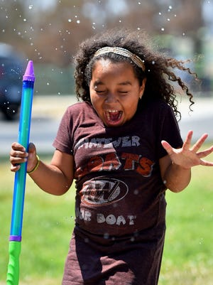 Ashley Bonilla, 8, reacts Tuesday as she is sprayed with water in Los Angeles.